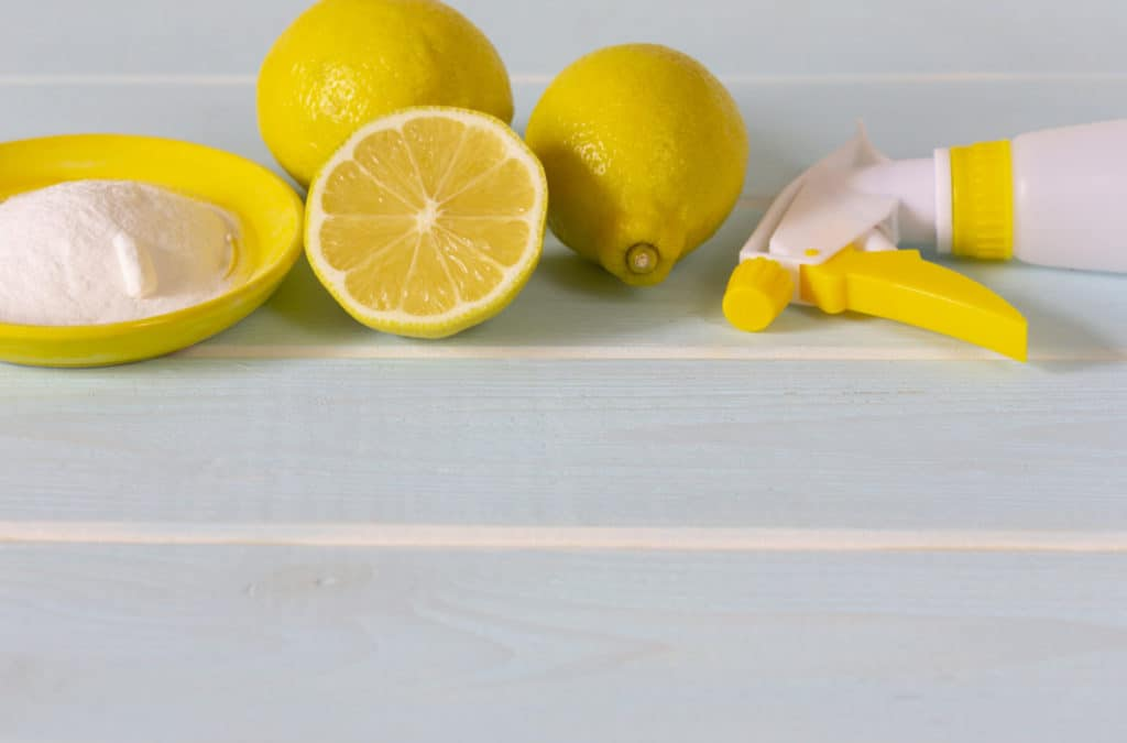 Natural products for eco cleaning. Lemon, baking soda and vinegar for eco housekeeping. All objects, lemon, bowl, pump sprayer  are in yellow color. Blue wooden background.