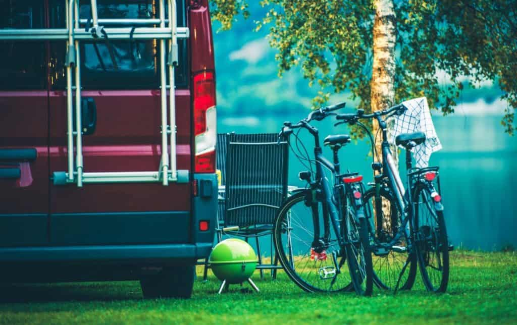 RV Camper Camping and Biking. Motorcoach and Two Bikes on the Campsite.